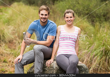 Portrait of a young couple sitting on a stone stock photo, Portrait of a young couple sitting on a stone in the nature by Wavebreak Media