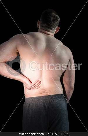 Strong bodybuilder with painful back stock photo, Strong bodybuilder with painful back on black background by Wavebreak Media