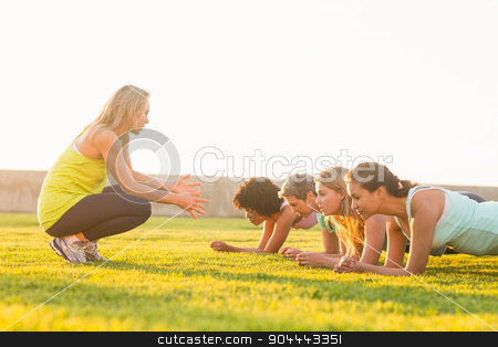 Sporty women planking during fitness class stock photo, Sporty women planking during fitness class in parkland by Wavebreak Media