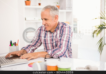 Smiling casual designer working with laptop stock photo, Smiling casual designer working with laptop in the office by Wavebreak Media