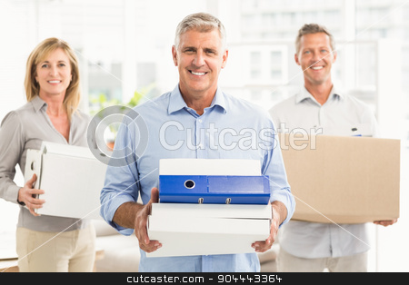Casual business people carrying cartons stock photo, Portrait of casual business people carrying cartons in the office by Wavebreak Media