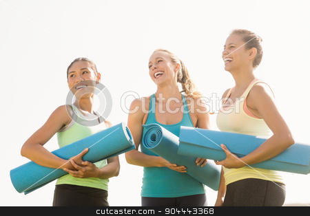 Laughing sporty women with exercise mats  stock photo, Laughing sporty women with exercise mats in parkland by Wavebreak Media