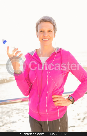 Smiling sporty woman with headphones holding bottle stock photo, Portrait of smiling sporty woman with headphones holding bottle at promenade by Wavebreak Media