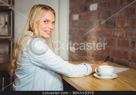 Smiling blonde writing on sheet of paper stock photo, Portrait of smiling blonde writing on sheet of paper at coffee shop by Wavebreak Media