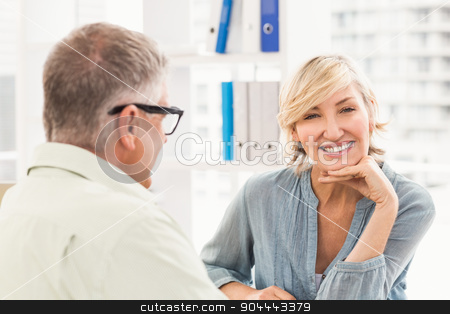 Smiling businesswoman looking at the camera stock photo, Portrait of a businesswoman with hands on chin at the office by Wavebreak Media