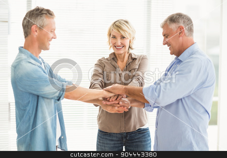 Smiling business colleagues stacking hands stock photo, Portrait of smiling business colleagues stacking hands at the office by Wavebreak Media