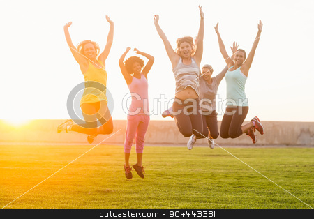 Happy sporty women jumping during fitness class stock photo, Portrait of happy sporty women jumping during fitness class in parkland by Wavebreak Media