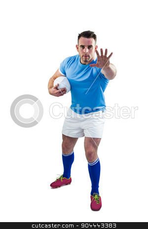 Rugby player looking at camera with hand up stock photo, Rugby player looking at camera with hand up on white background by Wavebreak Media