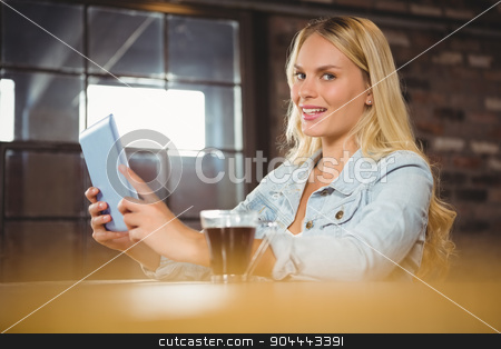 Smiling blonde having coffee and using tablet computer stock photo, Smiling blonde having coffee and using tablet computer at coffee shop by Wavebreak Media