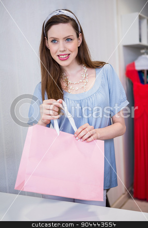Brunette at till with shopping bag stock photo, Brunette at till with shopping bag in fashion boutique by Wavebreak Media