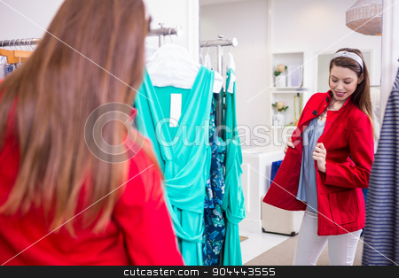 Brunette trying on a red coat stock photo, Brunette trying on a red coat in fashion boutique by Wavebreak Media