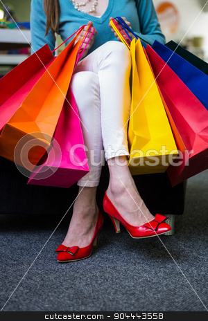 Woman holding many shopping bags stock photo, Woman holding many shopping bags in fashion boutique by Wavebreak Media