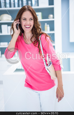 Pretty woman talking on phone while shopping stock photo, Pretty woman talking on phone while shopping at the pharmacy by Wavebreak Media