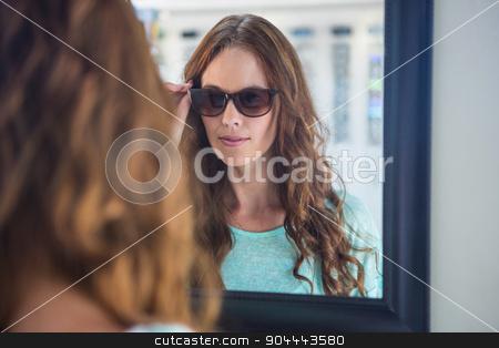 Pretty woman shopping for sunglasses stock photo, Pretty woman shopping for sunglasses at the optometry store by Wavebreak Media