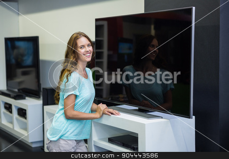 Pretty woman shopping for new television stock photo, Pretty woman shopping for new television at the electronics store by Wavebreak Media