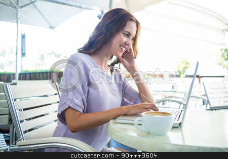 Woman enjoying a cappuccino using laptop stock photo, Woman enjoying a cappuccino using laptop on a sunny day by Wavebreak Media