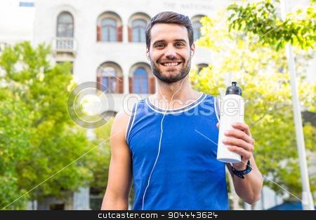 Handsome athlete smiling and holding bottle stock photo, Portrait of handsome athlete smiling and holding bottle in the city by Wavebreak Media