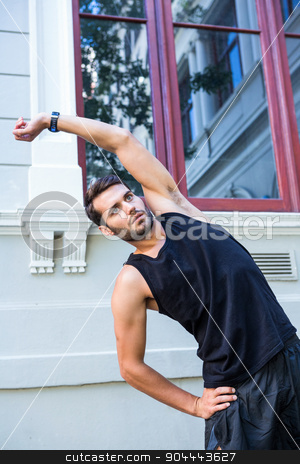 Handsome athlete stretching in front of a building stock photo, Handsome athlete stretching in front of a building in the city by Wavebreak Media