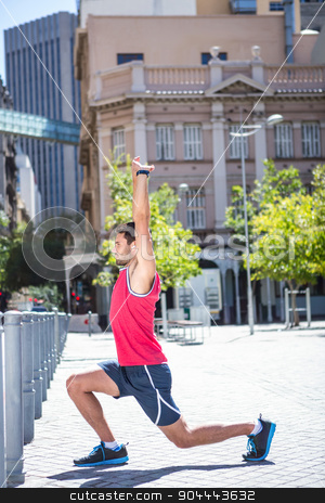 Handsome athlete doing body stretching stock photo, Side view of an handsome athlete doing body stretching on a sunny day by Wavebreak Media