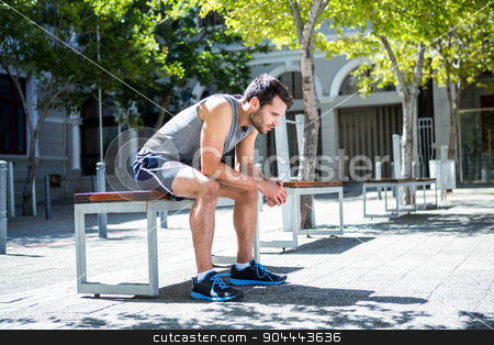 Exhausted athlete resting on a bench stock photo, Exhausted athlete resting on a bench on a sunny day by Wavebreak Media