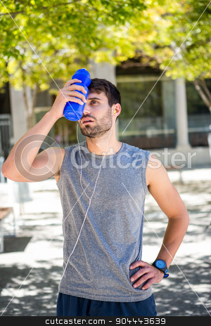 Exhausted runner putting a water bottle on head stock photo, Exhausted runner putting a water bottle on head on a sunny day by Wavebreak Media