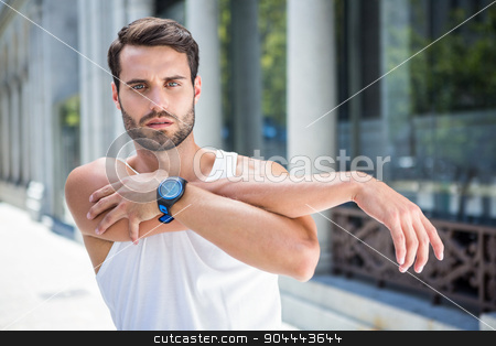 Focused handsome athlete stretching his arm stock photo, Focused handsome athlete stretching his arm in the city by Wavebreak Media