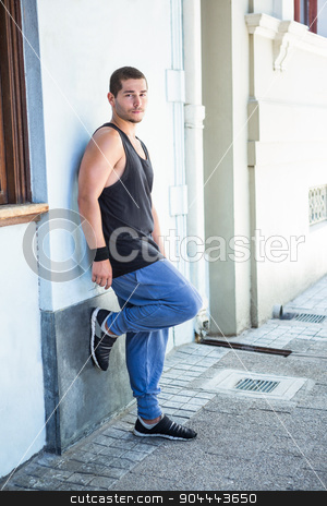 Portrait of a handsome athlete leaning against a wall stock photo, Portrait of a handsome athlete leaning against a wall on a sunny day by Wavebreak Media
