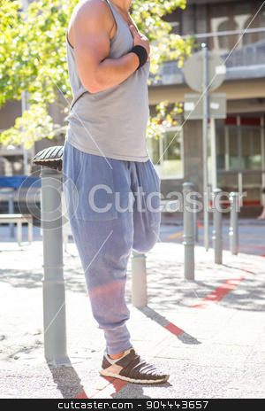 An handsome athlete stretching stock photo, An handsome athlete stretching on a sunny day by Wavebreak Media