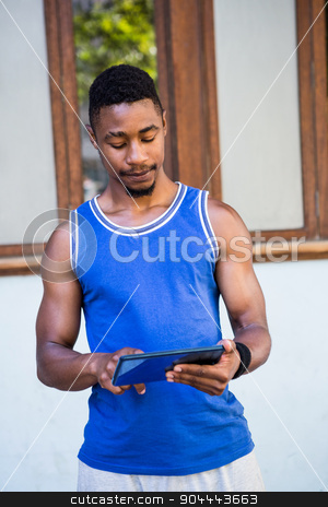 Smiling athletic man using tablet computer stock photo, Smiling athletic man using tablet computer in the city by Wavebreak Media