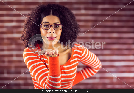 Attractive young woman sending kiss stock photo, Portrait of attractive young woman sending kiss against red brick background by Wavebreak Media