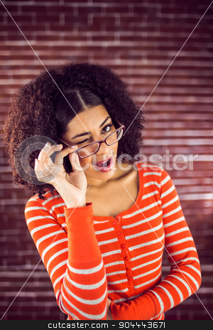 Attractive young woman winking stock photo, Portrait of attractive young woman winking against red brick background by Wavebreak Media