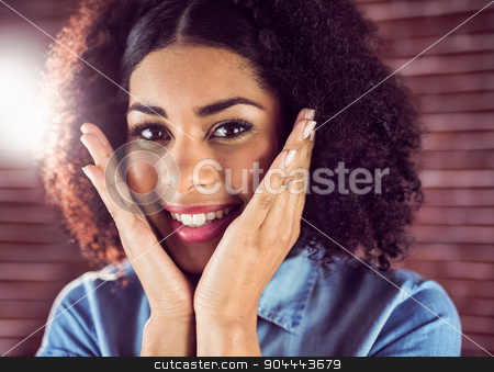 Attractive young woman being glad stock photo, Portrait of attractive young woman being glad against red brick background by Wavebreak Media