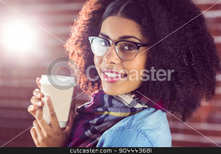 Smiling attractive hipster holding take-away cup stock photo, Portrait of smiling attractive hipster holding take-away cup against red brick background by Wavebreak Media