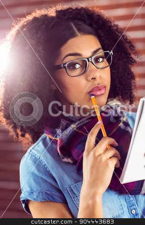 Attractive focused hipster taking notes stock photo, Portrait of attractive focused hipster taking notes against red brick background by Wavebreak Media