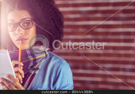 Daydreaming attractive hipster taking notes stock photo, Daydreaming attractive hipster taking notes against red brick background by Wavebreak Media