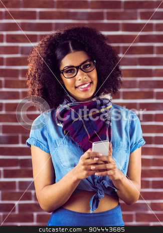 Smiling attractive hipster texting stock photo, Portrait of smiling attractive hipster texting against red brick background by Wavebreak Media