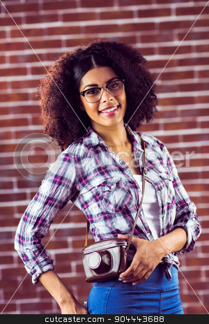 Attractive smiling hipster posing with camera stock photo, Portrait of attractive smiling hipster posing with camera against red brick background by Wavebreak Media