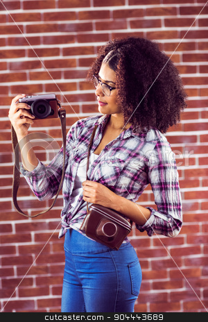Attractive hipster holding camera and looking at it stock photo, Attractive hipster holding camera and looking at it against red brick background by Wavebreak Media