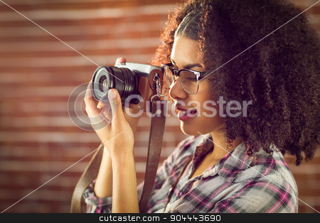 Attractive hipster photographing with camera stock photo, Attractive hipster photographing with camera against red brick background by Wavebreak Media