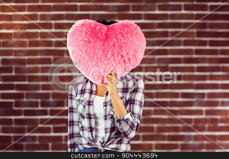 Young woman holding up heart-shaped pillow stock photo, Young woman holding up heart-shaped pillow against red brick background by Wavebreak Media