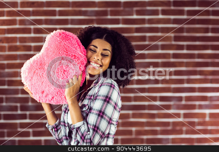 Attractive young woman cuddling with heart-shaped pillow stock photo, Attractive young woman cuddling with heart-shaped pillow against red brick background by Wavebreak Media