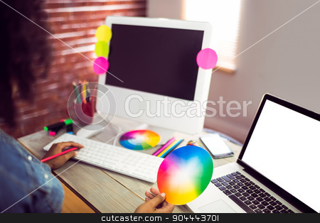 Casual female designer working with computer stock photo, Casual female designer working with computer against red brick background by Wavebreak Media