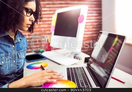 Casual female designer using laptop stock photo, Casual female designer using laptop at workplace by Wavebreak Media