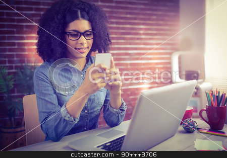 Casual businesswoman using her smartphone stock photo, Casual businesswoman using her smartphone in the office by Wavebreak Media