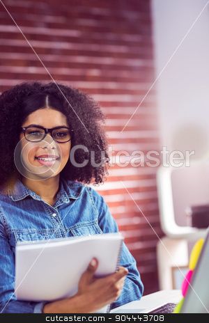 Casual businesswoman looking at reports stock photo,  Casual businesswoman looking at reports in the office by Wavebreak Media