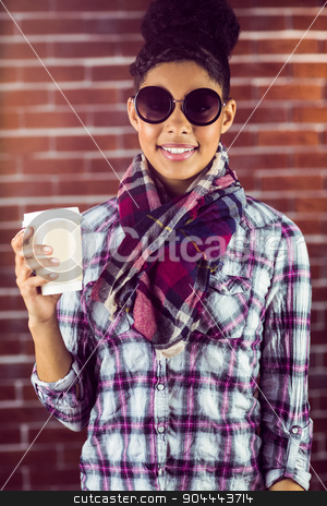 A female hipster holding a cup of coffee stock photo, A female hipster holding a cup of coffee against a brick wall by Wavebreak Media