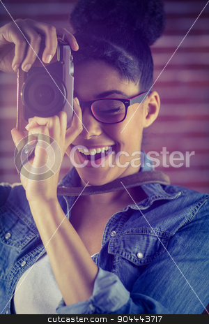 Young hipster taking a picture  stock photo, Young hipster taking a picture against a brick wall by Wavebreak Media