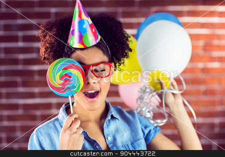 Young woman holding balloons and lollipop  stock photo, Young woman holding balloons and lollipop against a red brick wall by Wavebreak Media