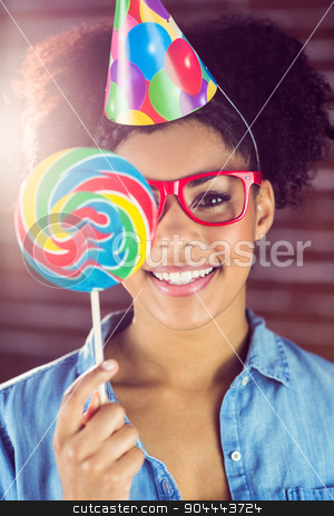 Portrait of a hipster hiding herself behind a lollipop stock photo, Portrait of a hipster hiding herself behind a lollipop against a brick wall by Wavebreak Media
