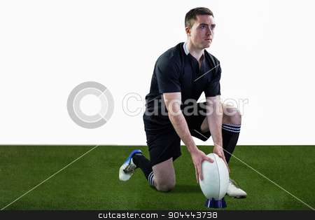 Rugby player ready to make a drop kick stock photo, Attentive rugby player ready to make a drop kick by Wavebreak Media